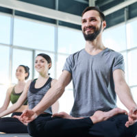 Group of young happy active people looking at yoga instructor while repeating one of exercises during workout
